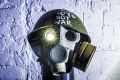 Art picture of a military gas mask on a white brick wall with shadows with flash with the inscription make photo not war on stock images