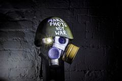 Art picture of a military gas mask on a white brick wall with shadows with flash with the inscription make photo not war on stock photos