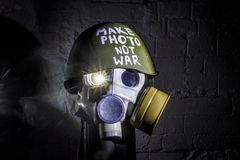 Art picture of a military gas mask on a white brick wall with shadows with flash with the inscription make photo not war on stock image