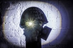 Art picture of a military gas mask on a white brick wall with shadows with flash with the inscription make photo not war on stock photography