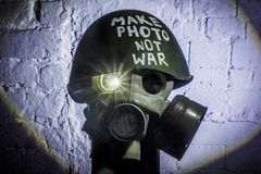 Art picture of a military gas mask on a white brick wall with shadows with flash with the inscription make photo not war on royalty free stock photos