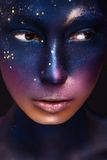 Art portrait of a beautiful girl with color paint on her face Royalty Free Stock Image