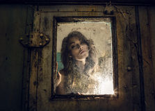 Art portrait of a beautiful young spooky woman, looks through grunge styled rainy window. Stock Images