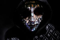 Art portrait of a hooded man with big rhinestones on his face. Mysterious mystical appearance of a man. Big crystals glisten in. The dark on the guy face stock photos