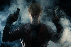 Art portrait man with two pistols in hands. In the smoke Stock Photos