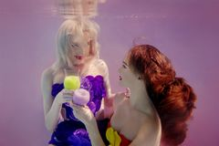 Art portrait of two beautiful pretty girls holding each other hands underwater. Art portrait of two beautiful pretty girls drinking cocktails underwater on pink Stock Image
