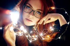 Art portrait of a woman with red hair in Christmas lights. Girl in glasses with reflected Christmas lights. Red hair in a yellow. Lights, tender feelings stock photos
