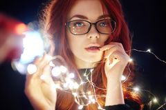 Art portrait of a woman with red hair in Christmas lights. Girl in glasses with reflected Christmas lights. Red hair in a yellow. Lights, tender feelings stock images