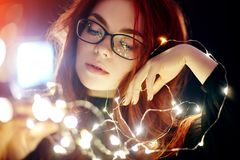 Art portrait of a woman with red hair in Christmas lights. Girl in glasses with reflected Christmas lights. Red hair in a yellow Royalty Free Stock Photo