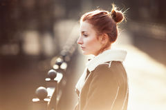 Art portrait of a young beautiful redhead woman on the bridge Royalty Free Stock Photo