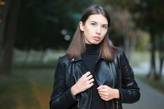 Art portrait of a young pretty brunette woman posing outdoors in black leather coat againt city park blurry background Royalty Free Stock Image