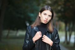 Art portrait of a young pretty brunette woman posing outdoors in black leather coat againt city park blurry background Stock Images