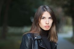 Art portrait of a young pretty brunette woman posing outdoors in black leather coat againt city park blurry background Stock Photo
