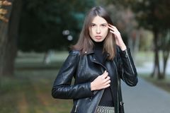 Art portrait of a young pretty brunette woman posing outdoors in black leather coat againt city park blurry background Royalty Free Stock Photos