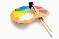 Art Pose. Paintbrushes on the palette with bright acrylic color Stock Images