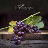 Art purple grapes  on old wooden background Stock Photos