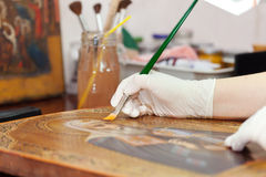 Art restorer works on ancient gilded icon Royalty Free Stock Images