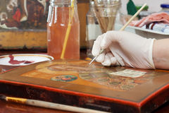Art  restorer works on icon with brush Stock Photos
