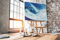 Art room. Artist workspace in painter studio. Painting on an easel among brushes and paints. Artist`s studio interior, workshop Royalty Free Stock Image