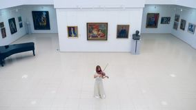 Art room with a female violinist playing the instrument. 4K stock video