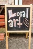Art Sale sign written on a blackboard. A blackboard om s stand is colored in to advertise local art for sale in Ocean Beach Fire Island Stock Image