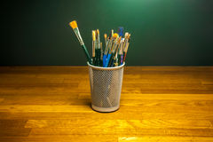 Art school brushes on wood studio desk Royalty Free Stock Photography