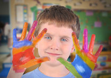 Art School Child with Painted Hands. A small preschooler boy is holding up his hands with rainbow paint on his fingers in an art class stock image