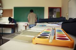 Art school classroom displaying watercolor paint box and chalkboard royalty free stock photo