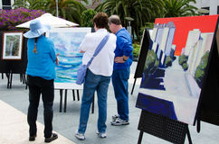 Art show in Union Square in San Francisco. Zanne Christensen (left) describes her painting to an interested couple at an outdoor art exhibit in Union Square held Stock Photo