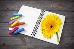 Art Sketchpad Color Flower. An art sketchpad with a yellow gerbera drawn on one page and color pastels on the other page,resting on an old wooden surface Royalty Free Stock Image