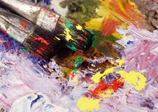 Art still life - closeup of two paintbrushes and dirty palette with colours Stock Images