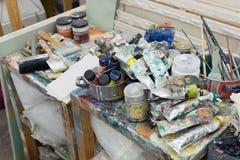 Art studio atelier table full of used artistic oil paint tube brush equipment workshop Stock Photo