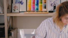 Art studio supplies paintings artist sketching. Art studio atmosphere. Neatly organized supplies paintings. Smiling lady artist sketching sitting at desk stock video footage
