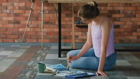Art studio workspace painter sit floor artwork. Art studio workspace. Painter sitting on the floor. Artwork collection on the wall stock video footage