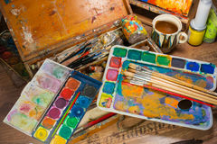 Art supplies in the atelier. Art supplies in the painter's atelier, colors and brushes Stock Photography