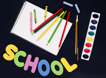 Art supplies for back to school. Back to school items - colored pencils, crayons, paintbrushes, paints, chalk, and sketchbook with the word 'school' on black Royalty Free Stock Photography