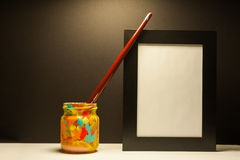 Art supplies brush and black frame in dramatic light with black background royalty free stock photography
