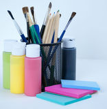 Paint, brushes, colored pencils and post it pads Stock Photography