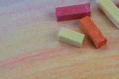 Art Supplies. Pink, orange, and yellow chalk pastels laying on a child's colored page Stock Photo