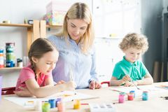 Art teacher and children in studio. Two kids, boy and girl, painting together with their art teacher at the table at art class royalty free stock images