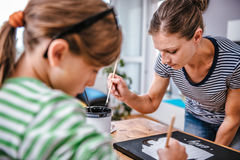 Art teacher helping a student with painting. Art teacher helping a student with her painting during art class royalty free stock images