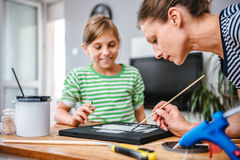 Art teacher helping a student with painting Stock Photo