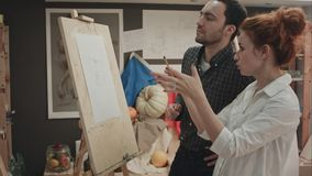 Art teacher and her apprentice discussing facial proportions on easel. Professional shot on BMCC RAW with high dynamic range. You can use it e.g. in your stock images