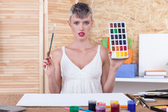 Art teacher with paint. Gorgeous woman with short hair is holding box of pain and a brush and looking to the camera. Concept of art class stock photo