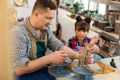 Art teacher sculpting animals out of clay with cute girl royalty free stock photos