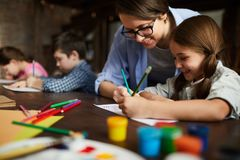 Art Teacher Working with Children. Portrait of smiling young women working with kids drawing in art class, copy space royalty free stock image