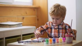 Art therapy for children. Psychology of the child`s personality. Help gaining confidence. Drawing. Creativity and. Education concept. Happy cute boy colors his stock footage