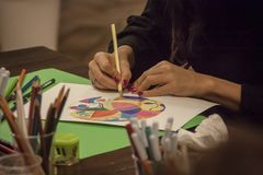 Art therapy school. Hands curated by a woman drawing a mandala at a table full of drawing objects in a school of art therapy stock photography