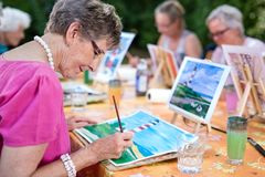 Art therapy for senior ladies, group of women painting the picture of lighthouse from the watercolor template sitting at table.