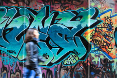 Art and transitioning. A woman walking pass a artistic grafiti wall Stock Images